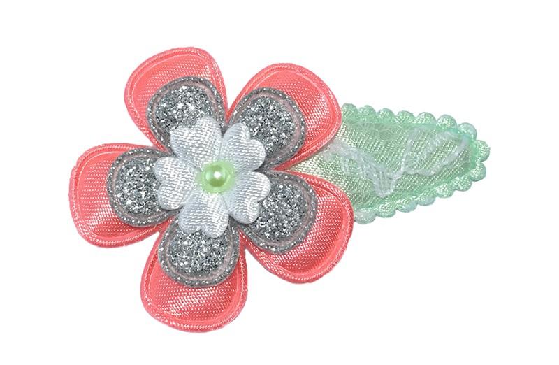 Vrolijk mint groen haarspeldje in kantlook met een koraal roze bloem, een zilver glinsterende bloem en een klein wit bloemetje. Afgewerkt met een klein licht groen pareltje.