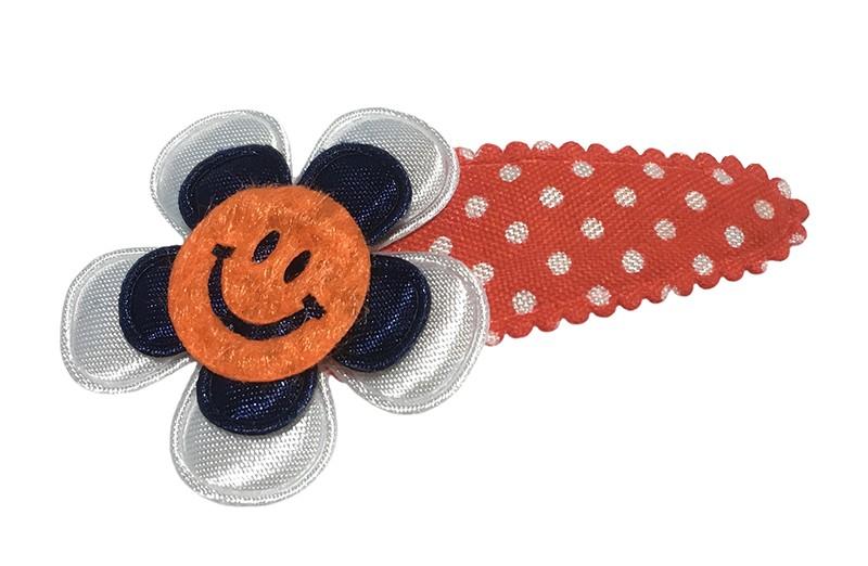 Vrolijk peuter kleuter haarspeldje rood met witte stippeltjes. met een wit bloemetje en een donkerblauw bloemetje. Afgewerkt met een vrolijke oranje smiley.