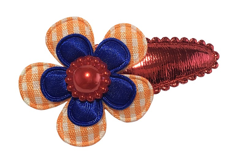 Hollands gekleurd! Glanzend rood peuter haarspeldje.  Met daarop en oranje geruit bloemetje en een effen kobalt blauw bloemetje.  Afgewerkt met een rood pareltje.
