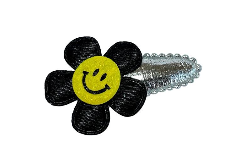 Vrolijk zilver glanzend peuter meisjes haarspeldje.  Met een effen zwart bloemetje en een gele smiley.