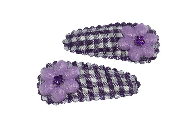 Vrolijk setje van 2 paars geruite baby peuter haarspeldjes. Met op elk een klein lila paars bloemetje en een klein wit pareltje.