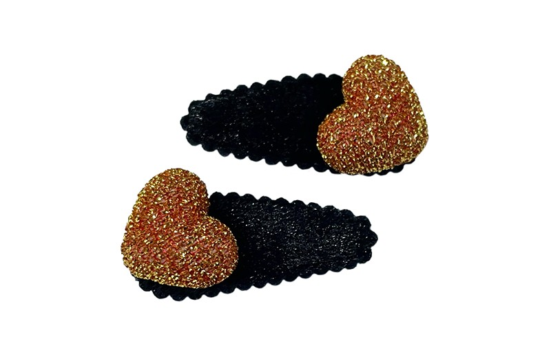 Vrolijk setje van 2 zwarte baby peuter haarspeldjes.  Met op elke een oranjebruin glitter hartje.