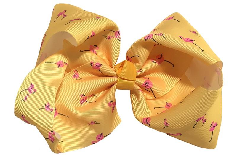 Vrolijke extra, extra grote haarstrik van geel lint.  Met leuk roze flamingo printje.  Op een handige haarknip met tandjes van 8 centimeter.  Extra groot model. Ook leuk voor bijvoorbeeld een themafeestje.