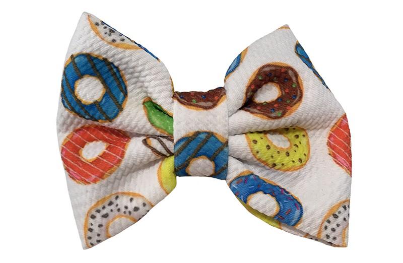 Vrolijke extra grote stoffen haarstrik. Met vrolijke gekleurde donut motiefjes.  Op een handige haarknip met kleine tandjes van ongeveer 5.5 centimeter.