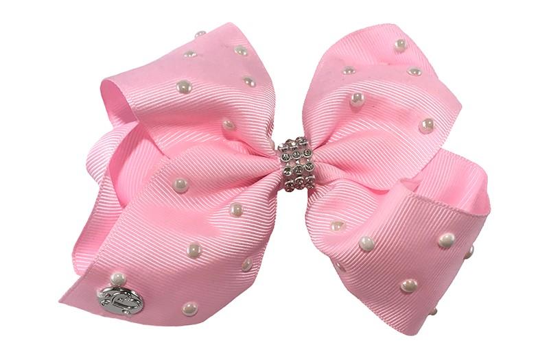 Schattige grote licht roze haarstrik van lint.  Met kleine witte paretjes op het lint en in het midden een pareltjes bandje.  De strik is vast gemaakt op een handige haarknip met kleine tandjes van 7.5 centimeter.