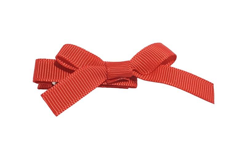Leuk haarknipje bekleed met rood lint. Met daarop een vrolijk strikje van rood lint. Het knipje is een alligator haarknipje van ongeveer 4 centimeter.