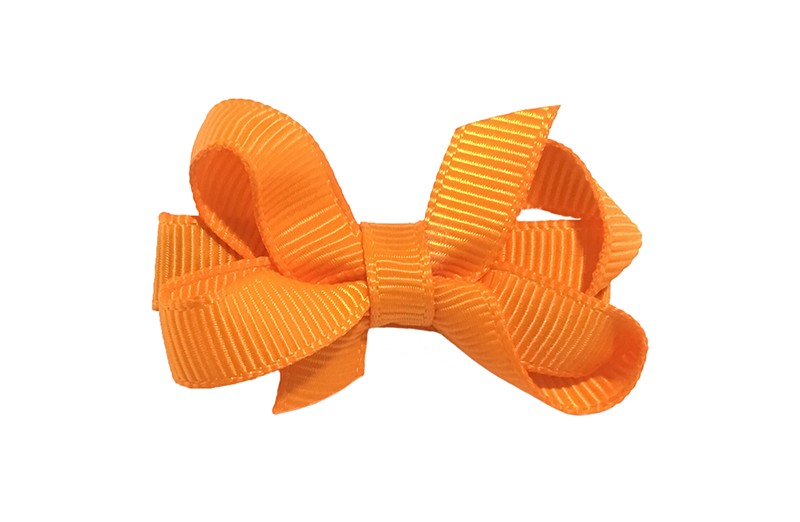 Lief klein haarknipje met een mooi strikje van oranje geribbeld lint. Op een alligatorknipje bekleed oranje lint.