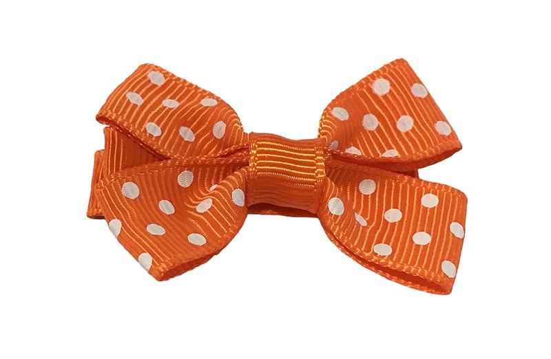 Leuk oranje haarstrikje met witte stippeltjes. Van geribbeld lint.  Op een platte haarknip van ongeveer 4.5 centimeter bekleed met oranje lint.