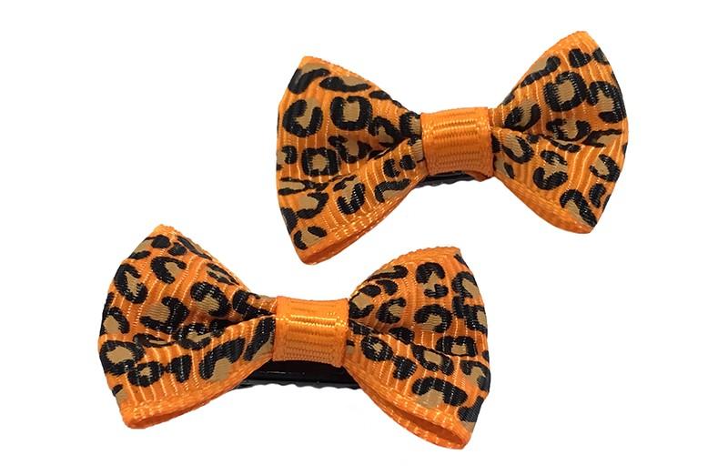 Vrolijk setje van 2 kleine oranje haarstrikjes met luipaard printje.  Op een klein zwart alligatorknipje van 3 centimeter.
