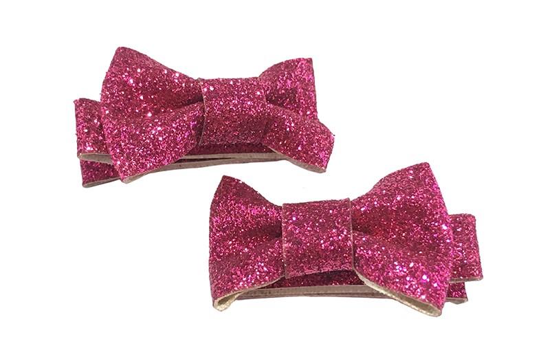 Vrolijk setje van 2 fel roze glitter haarstrikjes. Op een alligatorknipje van ongeveer 3.5 bekleed met glitterlint.