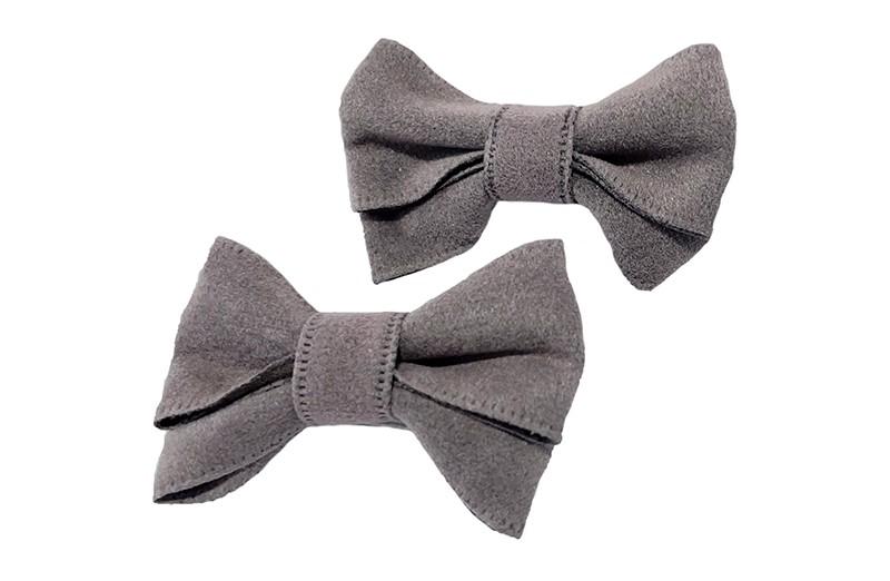 Schattig setje van 2 taupe grijze suedelook strikjes.  Op een haarknipje met kleine tandjes. Bekleed met lichtgrijs lint.  Het knipje is ongeveer 3.5 centimeter.