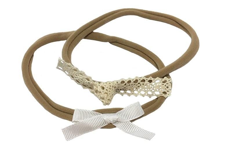Schattig setje van 2 nylon baby haarbandjes.  1 haarbandje met een wit lint strikje.  1 haarbandje met een wit geknoopt kantje.  De haarbandjes zijn van rekbaar nylon, geschikt tot ongeveer 15 maanden.  Het lint strikje is ongeveer 6 centimeter en het kantknoopje is ongeveer 9 centimeter.