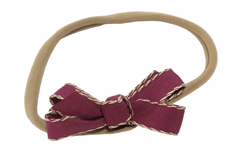 Schattig goed rekbaar nylon baby haarbandje. Met een strikje van geribbeld bordeaux rood lint. Het haarbandje is van goed rekbaar nylon geschikt tot ongeveer 18 maanden.  Het strikje is ongeveer 7 centimeter breed.