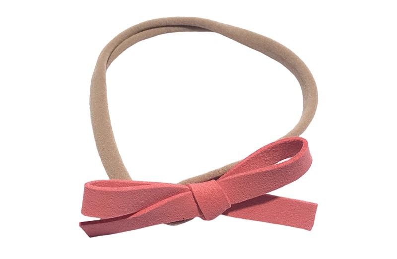 Leuk! Nylon haarbandje met koraal roze suedelook strikje.  Het nylon haarbandje is heel goed rekbaar en daardoor geschikt voor baby, peuter en kleuter meisjes.  Leuk in heel veel kapseltjes!  Het suede strikje is ongeveer 8 centimeter breed.