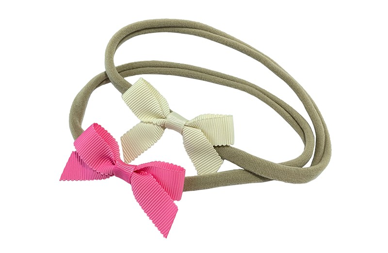 Schattig setje van 2 goed rekbare nylon haarbandjes. Met op elk een klein strikje van geribbeld lint.  1 haarbandje met een roze strikje.  1 haarbandje met een wit strikje.  De haarbandjes zijn van goed rekbaar nylon, geschikt tot ongeveer 6 jaar.  De strikjes zijn ongeveer 6 centimeter breed.