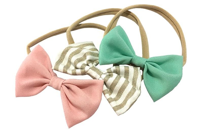 Vrolijk setje van 3 rekbare nylon baby peuter haarbandjes.  1 nylon haarbandje met een mint groen stoffen strikje.  1 nylon haarbandje met een stoffen strikje goud bruin met wit gestreept.  1 nylon haarbandje met een licht roze stoffen strikje. De strikjes zijn elk ongeveer 8 centimeter breed.