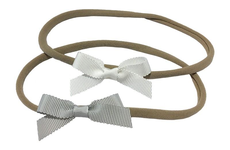 Schattig setje van 2 goed rekbare nylon haarbandjes. Met op elk een klein strikje van geribbeld lint.  1 haarbandje met een wit strikje.  1 haarbandje met een licht grijs strikje.  De haarbandjes zijn heel goed rekbaar en daardoor geschikt tot ongeveer 6 jaar.  De strikjes zijn ongeveer 6 centimeter breed.
