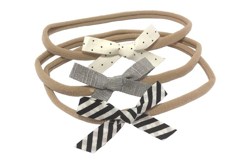 Schattig setje van 3 rekbare nylon baby haarbandjes.  1 nylon haarbandje met een zwart wit gestreept strikje.  1 nylon haarbandje met een wit strikje met zwarte stippeltjes.  1 nylon haarbandje met een grijs strikje.