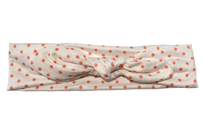 Leuk wit stoffen baby haarbandje.  Met een vrolijke oranje rode stipjes.  Het haarbandje is van zachte gladde stof.  Geknoopt in een leuk modelletje.