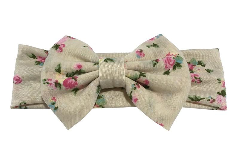 Vrolijke creme/zandkleurige grotere meisjes haarband met roze bloemetjes motiefjes.  Deze haarband is van zachte rekbare stof.  Met een grote stoffen strik van ongeveer 8 centimeter hoog.