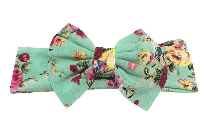 Leuke licht groene grotere meiden haarband van zachte comfortabele stof.  Met vrolijke roze bloemen motiefjes. Met een mooie strik in hetzelfde dessin. De strik is ongeveer 8 centimeter breed.  Deze haarband is van zachte goede rekbare stof.