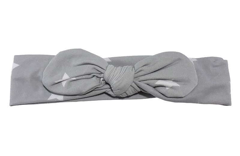 Vrolijk licht grijs peuter meisjes haarbandje met witte sterretjes.  Het haarbandje is van zachte rekbare stof geknoopt in een leuk modelletje.  Het haarbandje is niet uitgerekt ongeveer 21 centimeter.  En 4.5 centimeter hoog.