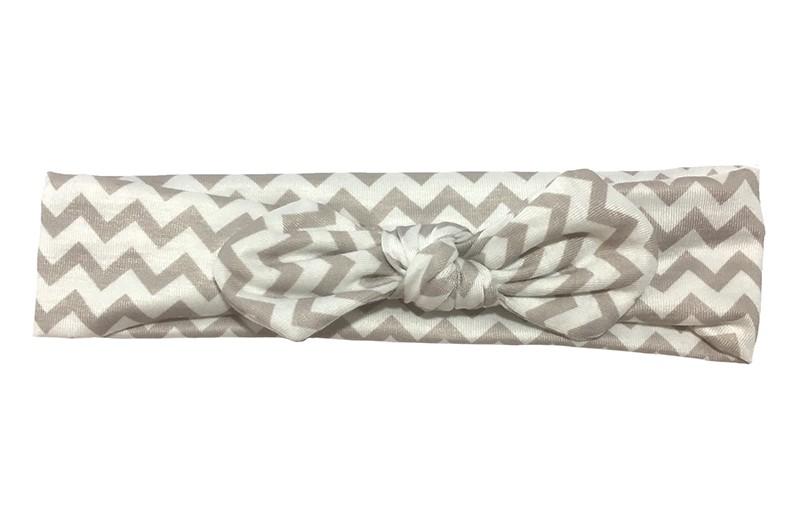 Vrolijk wit met (taupe) grijs baby peuter haarbandje. Met een leuk zigzag patroontje.  Het haarbandje is van zachte rekbare stof. Geknoopt in een leuk modelletje.
