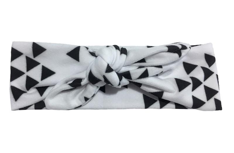 Leuk baby, peuter, meisjes knoop haarbandje. Van zachte witte stof met zwarte driehoekmotiefjes erop. Dit haarbandje is van rekbare stof en heel makkelijk zelf te knopen zo kun je lang plezier hebben van dit leuke haarbandje.  Het haarbandje is ongeveer 5.5 centimeter breed.