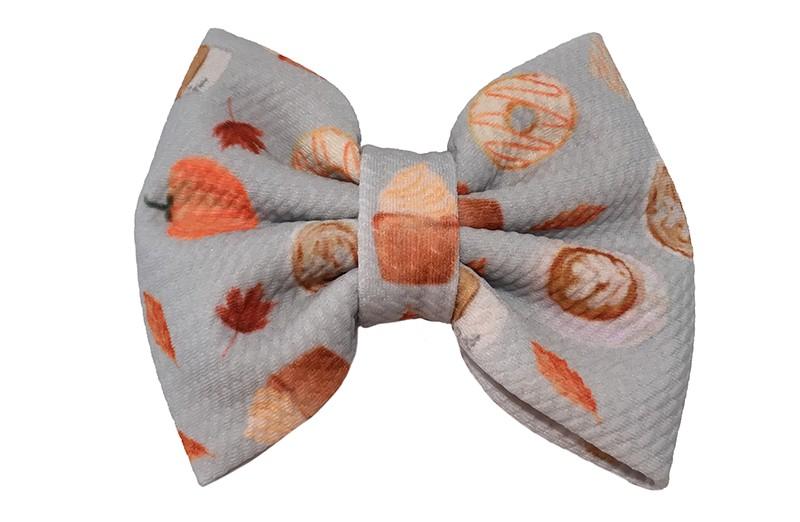 Vrolijke extra grote grijze stoffen haarstrik. Met Oranje herfstfiguurtjes.  Op een handige haarknip met kleine tandjes van ongeveer 5.5 centimeter.