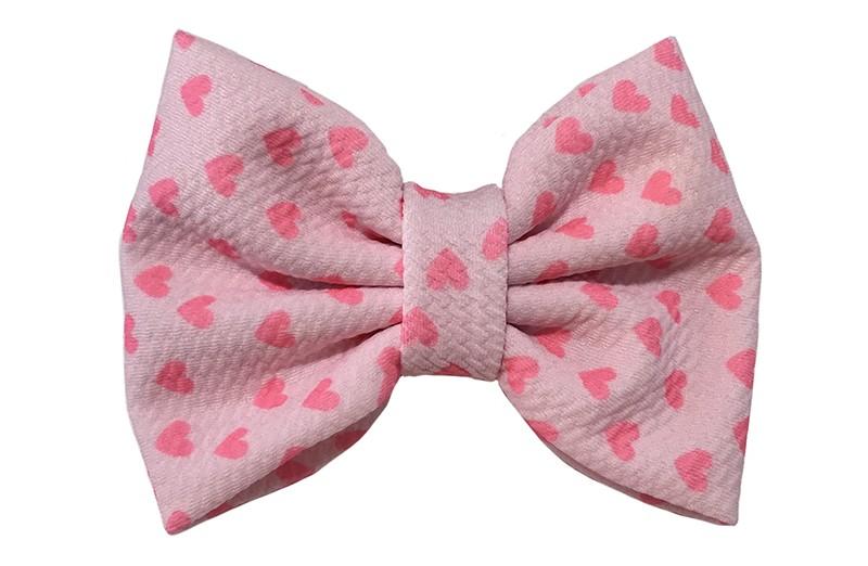 Vrolijke extra grote lichtroze stoffen haarstrik. Met fel roze hartjes.  Op een handige haarknip met kleine tandjes van ongeveer 5.5 centimeter.
