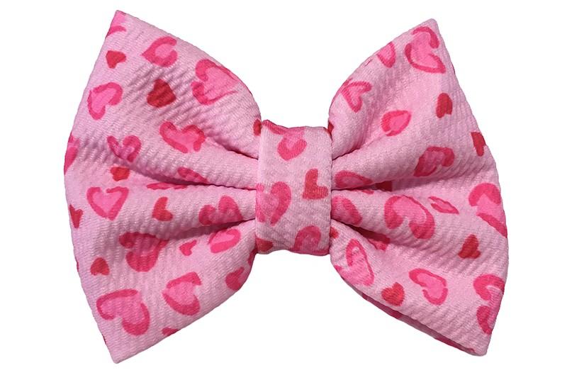 Vrolijke extra grote lichtroze stoffen haarstrik. Met een roze hartjes.  Op een handige haarknip met kleine tandjes van ongeveer 5.5 centimeter.