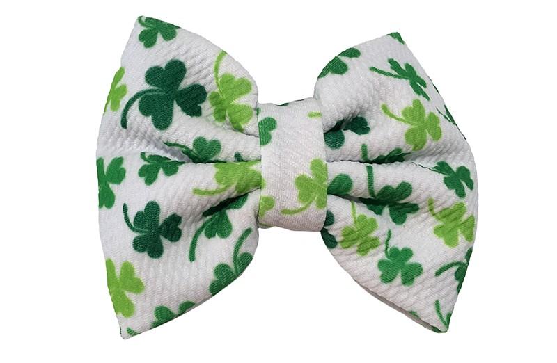 Vrolijke extra grote stoffen haarstrik. Van een mooie witte stof met groene blaadjes.  Op een handige haarknip met kleine tandjes van ongeveer 5.5 centimeter.