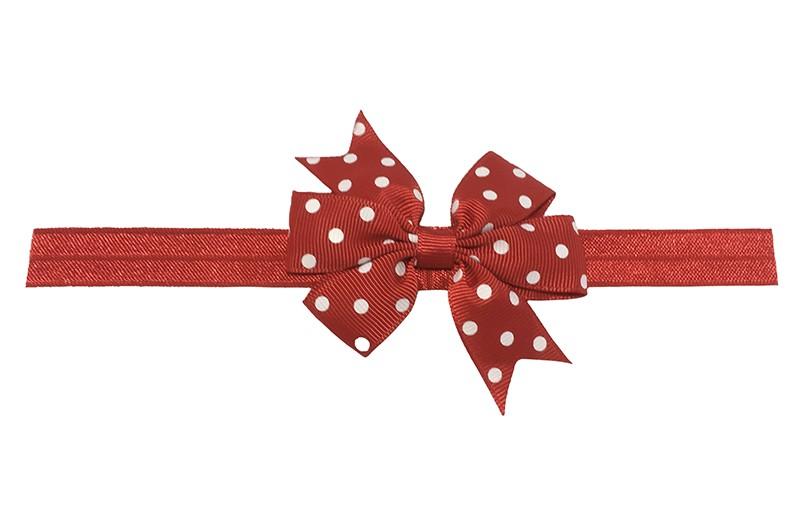 Vrolijk rood baby haarbandje. Met een rode strik met witte stippeltjes. De strik is ongeveer .. centimeter.  Het haarbandje is van rekbaar elastiek. Niet uitgerekt is het haarbandje ongeveer 18.5 centimeter.