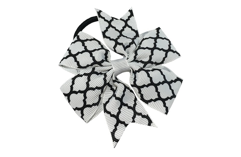 Stevige zwarte haarelastiek met een witte strik van lint met vrolijk zwart lijntjes patroontje,  Leuk in allerlei peuter en kleuter kapseltjes