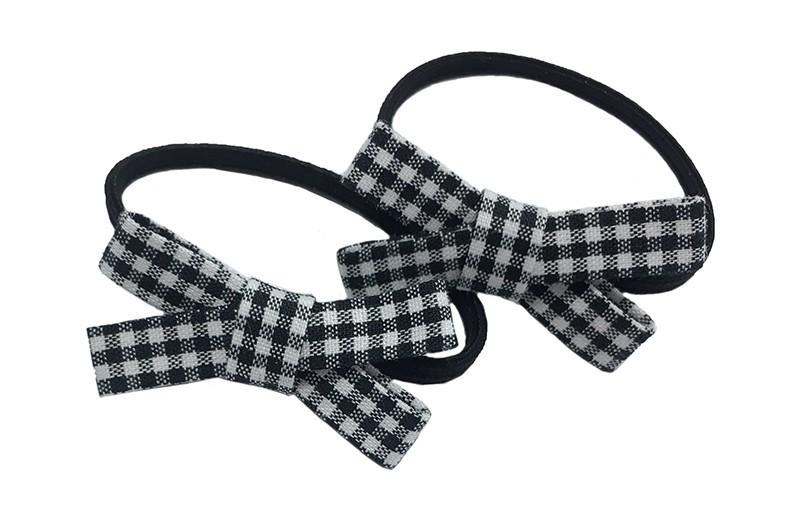 Lief setje van 2 smalle zwarte haarelastiekjes. Met op elk een zwart wit geruit stoffen strikje. De strikjes zijn ongeveer 3.5 centimeter breed.