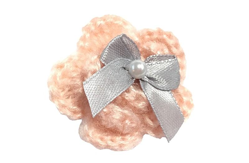 Volijke haarknip met een zalm roze gehaakte bloem. Met daarop een grijs strikje en een klein wit pareltje.