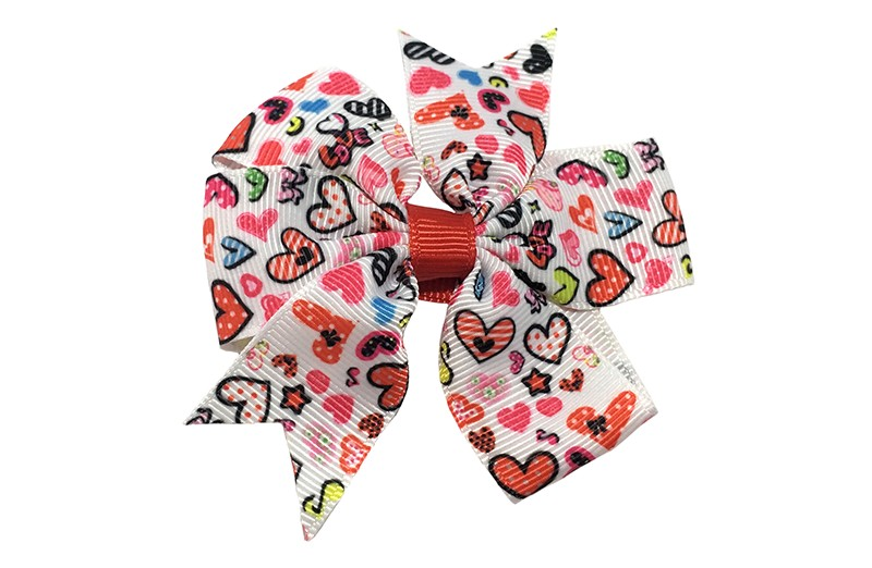 Vrolijke grote witte haarstrik met hartjes motiefjes in verschillende vrolijke kleurtjes.  Op een platte haarknip bekleed met rood lint.