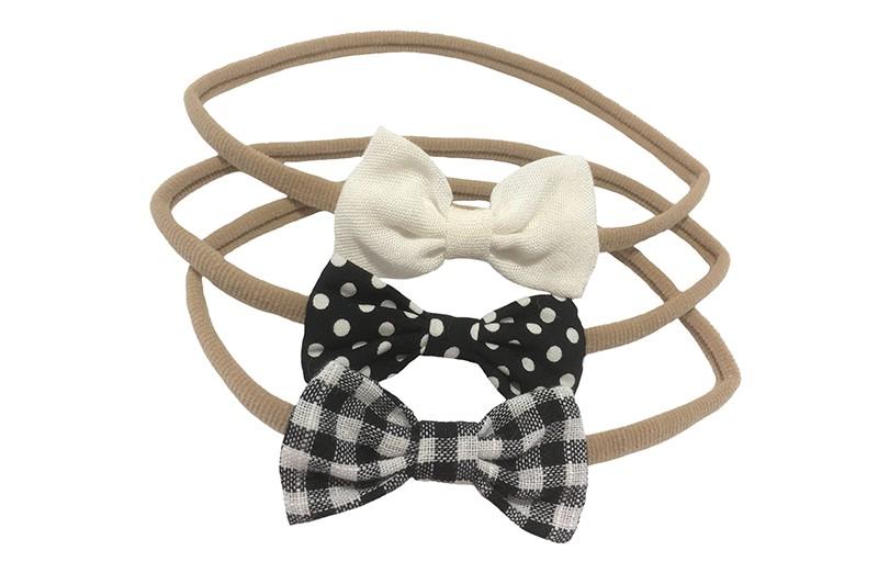 Schattig setje van 3 rekbare nylon baby haarbandjes.  1 nylon haarbandje met een wit stoffen strikje.  1 nylon haarbandje met een zwart stoffen strikje met witte stippels.  1 nylon haarbandje met een zwart wit geruit stoffen strikje.