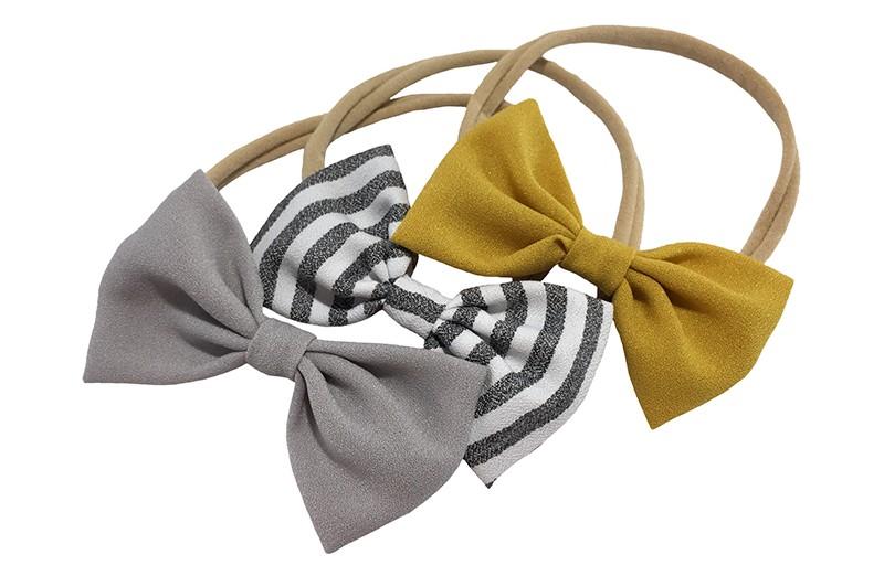 Vrolijk setje van 3 rekbare nylon baby peuter haarbandjes.  1 nylon haarbandje met een grijs stoffen strikje.  1 nylon haarbandje met een stoffen strikje wit grijs gestreept.  1 nylon haarbandje met een okergeel stoffen strikje. De strikjes zijn elk ongeveer 8 centimeter breed.